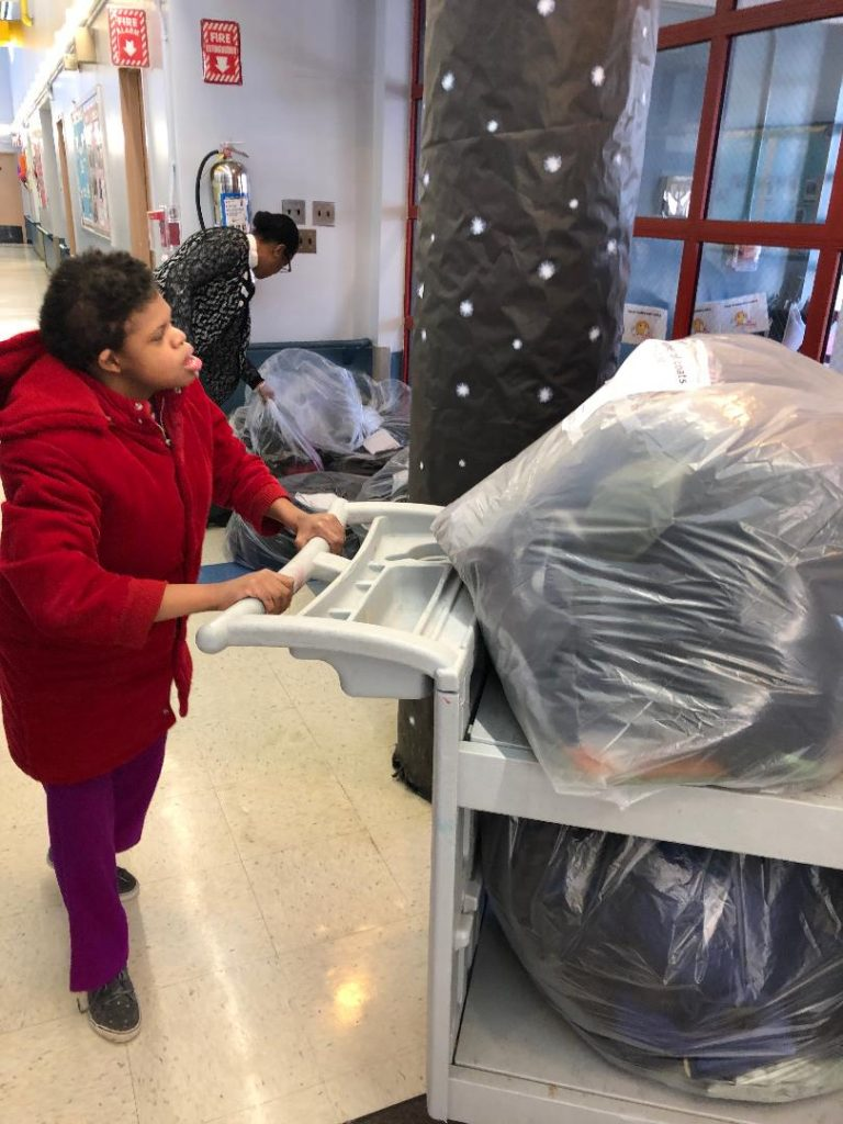 Student collecting coats for the coat drive.