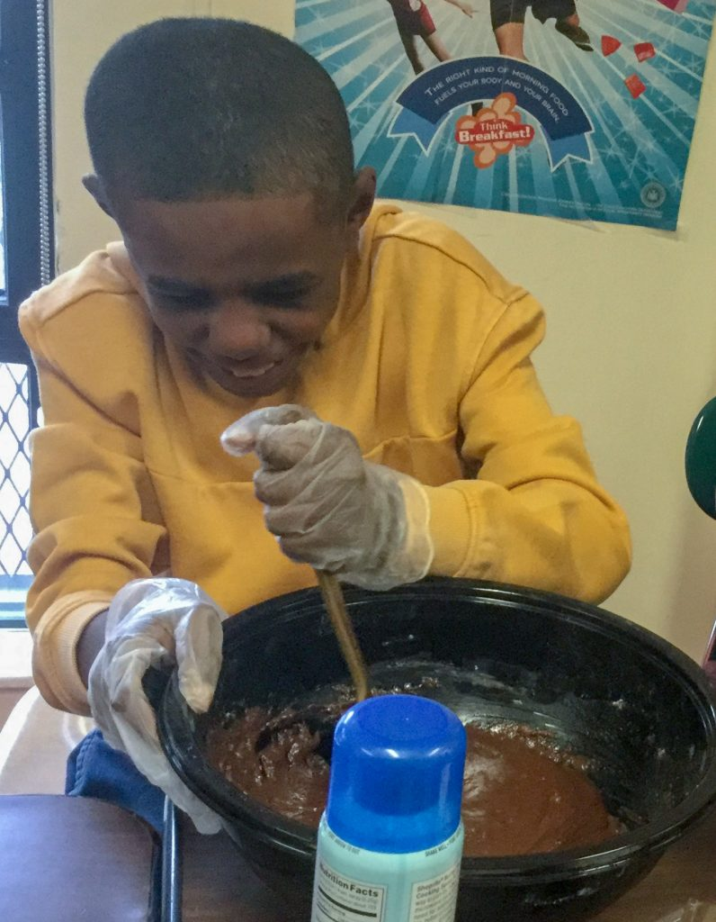 Student stirring during a cooking lesson.