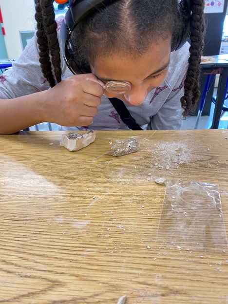 Isabel is using a magnifying glass to examine her fossil.